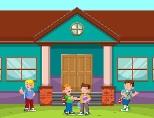 Niños de regreso a la escuela y hablando frente a la escuela.