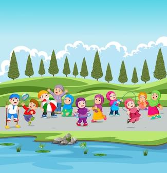 Los niños y sus padres están de vacaciones en el jardín cerca del río.
