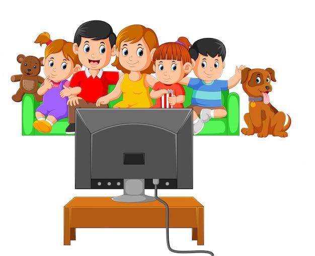 Los niños con sus padres están viendo la televisión juntos.