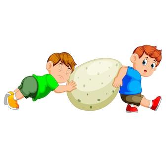 Los niños tiran y mueven el gran huevo de dinosaurio verde.