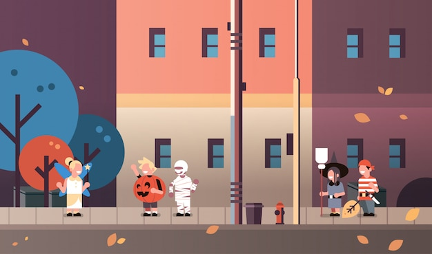 Niños vestidos de monstruos hada calabaza pirata momia bruja disfraces caminando fondo de la ciudad
