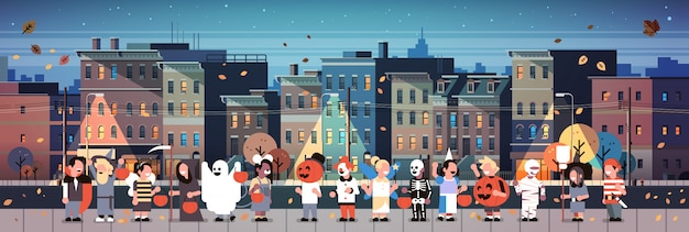 Niños vestidos con trajes de monstruos caminando noche ciudad banner