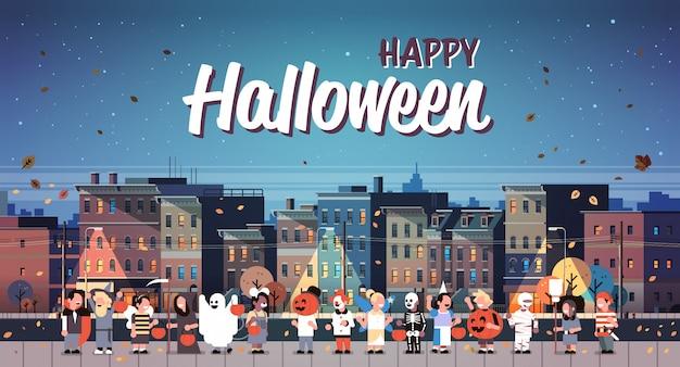 Niños vestidos con trajes de monstruos caminando noche ciudad vacaciones banner