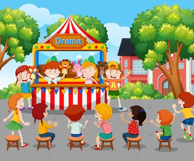 Niños viendo un espectáculo de marionetas afuera.