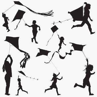 Niños volando cometas siluetas