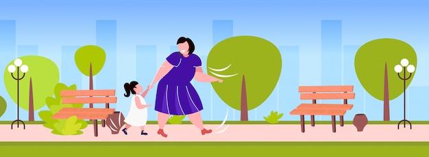 Obesa gorda madre con hija cogidos de la mano sobrepeso mujer y niño caminando familia al aire libre divirtiéndose obesidad concepto parque urbano paisaje urbano fondo horizontal de longitud completa