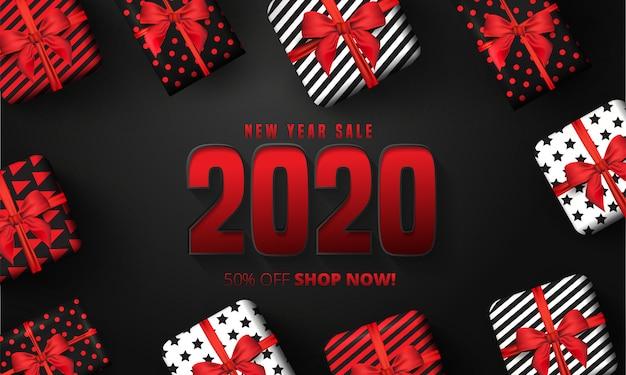 Oferta de 50% de descuento para 2020 letras de venta de feliz año nuevo, cajas de regalo alrededor sobre fondo negro.