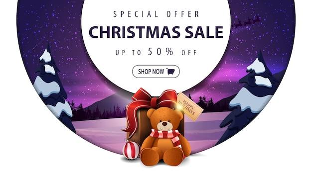 Oferta especial, rebajas navideñas, hasta 50, banner de descuento blanco con grandes anillos decorativos, paisaje invernal y regalo con osito de peluche