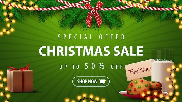 Oferta especial, venta de navidad, hasta 50% de descuento, hermoso banner de descuento verde con ramas de árboles de navidad, guirnaldas y galletas con un vaso de leche para santa claus