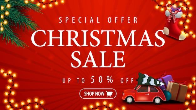 Oferta especial, venta de navidad, hasta 50% de descuento, pancarta de descuento roja con guirnalda, ramas de árboles de navidad, medias navideñas y auto rojo antiguo con árbol de navidad