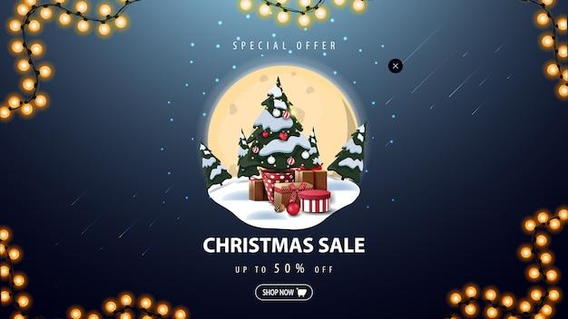 Oferta especial, venta de navidad, banner de descuento azul con gran luna llena, ventisqueros, pinos, cielo estrellado y árbol de navidad en una maceta con regalos