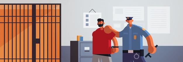 Oficial arrestado policía criminal en uniforme sosteniendo atrapado sospechoso ladrón autoridad de seguridad justicia ley servicio concepto moderno departamento de policía interior plano retrato horizontal