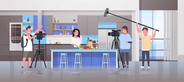 Los operadores que utilizan la cámara de video de grabación de alimentos blogger mujer preparando sabrosos platos camarógrafos con equipos profesionales de cocina blog de producción de películas concepto cocina interior horizontal