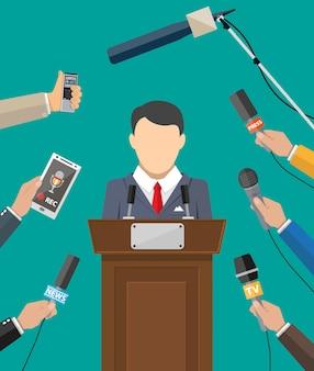 Orador público y manos de periodistas.