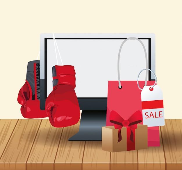 Ordenador y guantes de boxeo y bolso de compras sobre madera y blanco