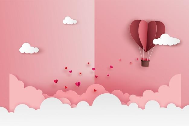 Origami globo corazón volando con muchos mini corazones en el cielo sobre la nube en el día de san valentín.