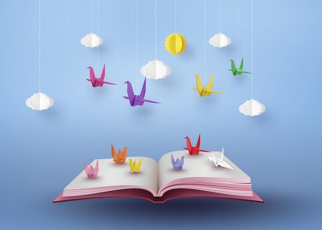 Origami hizo pájaro de papel colorido volando sobre libro abierto