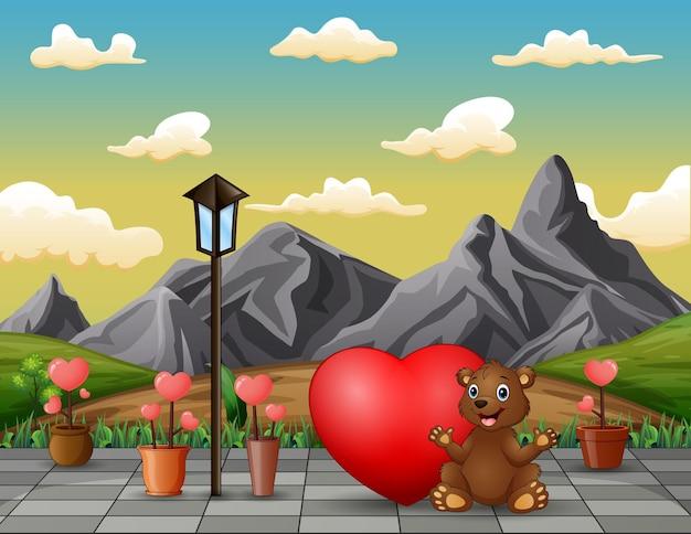 Un oso sentado con corazón rojo en el paisaje del parque.