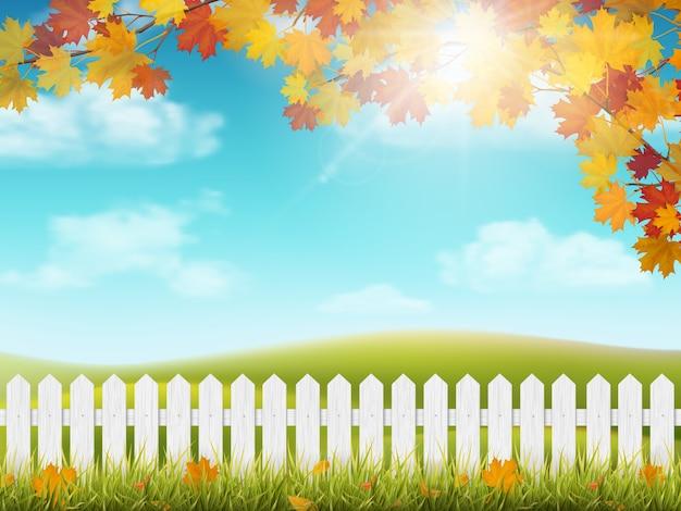 Otoño paisaje rural con valla de madera blanca. rama de árbol de arce con hojas de colores. hierba y hojas caídas. ver en prado con colinas y cielo con nubes y sol.