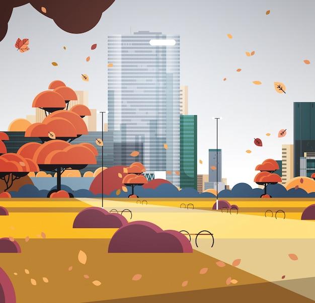 Otoño parque urbano horizonte de la ciudad con hojas amarillas que caen en la luz del sol skyskraper edificios paisaje urbano