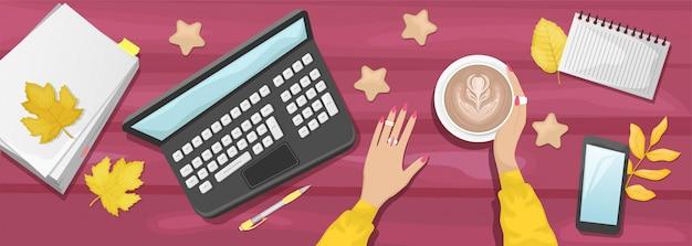 Otoño plano pone fondo con lugar de trabajo en un café. manos de mujer sosteniendo una taza de capuchino. fondo de madera de borgoña con hojas amarillas de otoño. laptop, notebook, teléfono inteligente, cookie