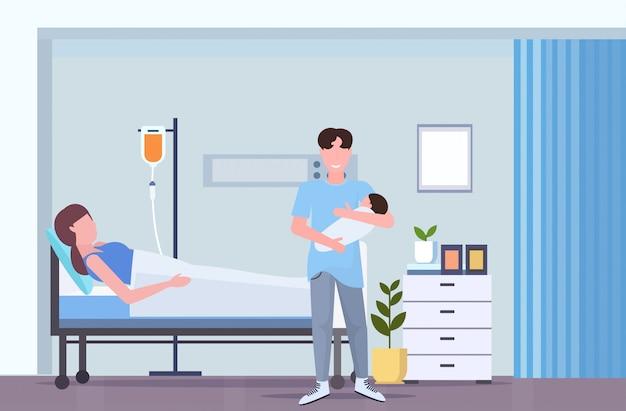 Padre sosteniendo al bebé recién nacido hombre visitando a su esposa acostada en la cama del hospital con gotero feliz familia paternidad concepto de maternidad sala de maternidad interior longitud completa horizontal