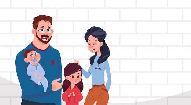 Padres de familia jóvenes con dos hijos, hija e hijo de pie sobre fondo de pared de ladrillo blanco