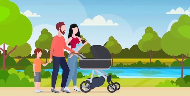Padres jóvenes empujando el cochecito caminando con niños al aire libre familia feliz divirtiéndose juntos concepto de paternidad hermoso parque paisaje fondo horizontal de longitud completa