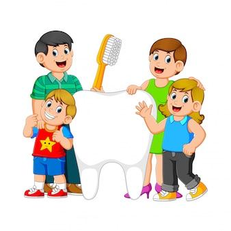 Padres sonrientes con dos niños de pie junto al gran diente blanco que sostiene el cepillo de dientes