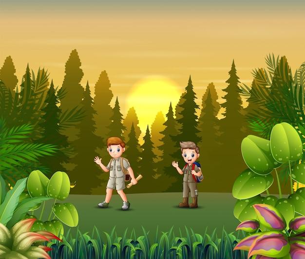 Paisaje al atardecer con niños exploradores en el bosque