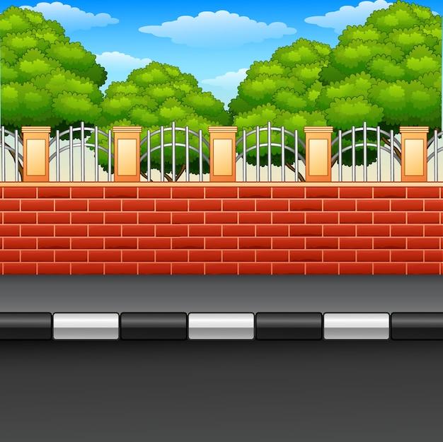 Paisaje de una calle con vallas de ladrillo y plantas verdes