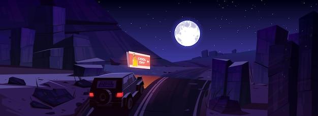 Paisaje desértico nocturno con coche en carretera, cartelera y luna en el cielo.