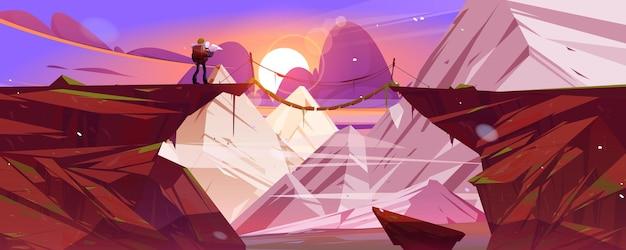 Paisaje de montaña al atardecer con hombre excursionista y puente colgante