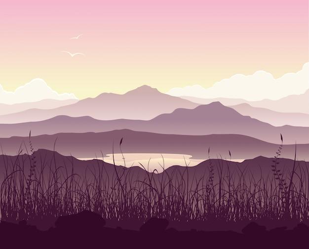 Paisaje de montaña con césped y enorme lago.