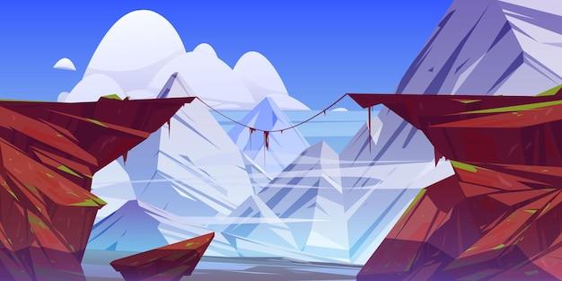 Paisaje de montaña con precipicio en rocas y picos nevados.