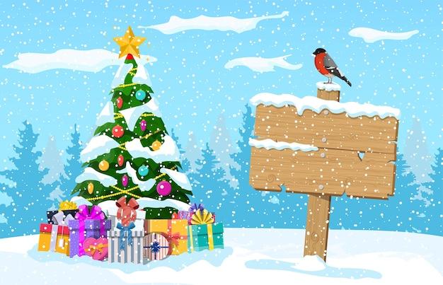 Paisaje navideño con árbol, cajas de regalo y cartel de madera con pájaro camachuelo. paisaje invernal con bosque de abetos y nevando. celebración de año nuevo vacaciones de navidad.