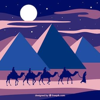 Paisaje nocturno de diseño plano con pirámides egipcias y caravana de camellos