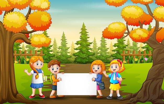 Paisaje del parque otoñal con niños de la escuela con cartel en blanco