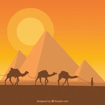 Paisaje de pirámides con caravana