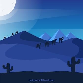 Paisaje con piramides de egipto y caravana de camellos en la noche