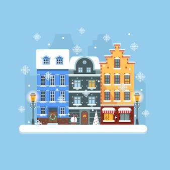 Paisaje plano de la calle de invierno de europa con coloridas casas de estilo europeo y adornos navideños.