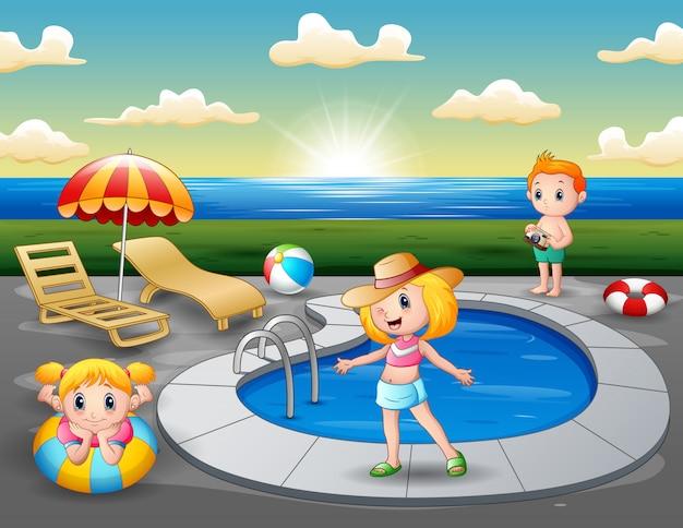 Paisaje de playa con niños junto a la mini piscina