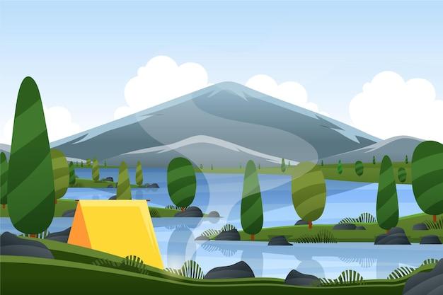 Paisaje primaveral con camping y montaña.