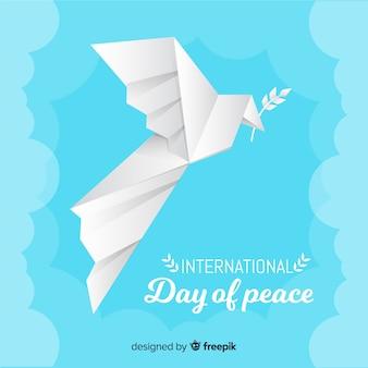 Paloma de origami para el día de la paz con hoja de olivo