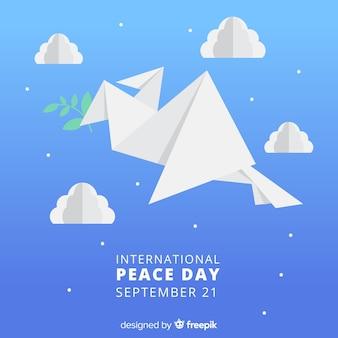 Paloma origami sosteniendo rama rodeada de nubes y estrellas