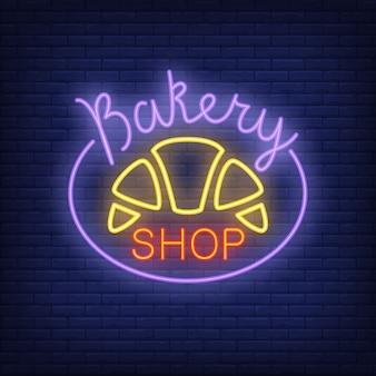 Panadería, tienda, neón, señal cruasán brillante en la pared de ladrillo azul oscuro.