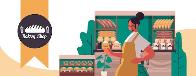 Panadero de sexo femenino en uniforme que vende productos de panadería frescos en la ilustración de vector horizontal de retrato de tienda