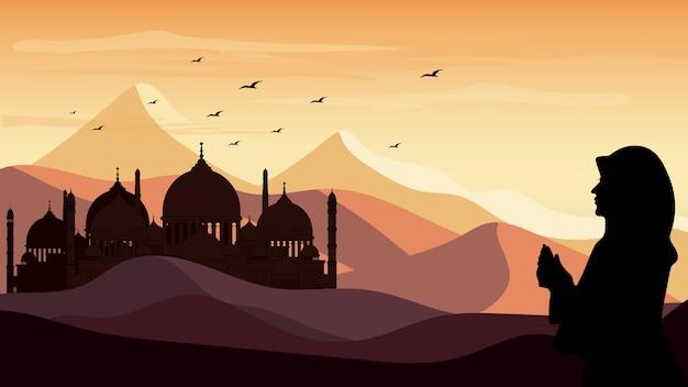 Panorama del paisaje silueta de una mujer rezando en el fondo del desierto durante el mes de ramadán