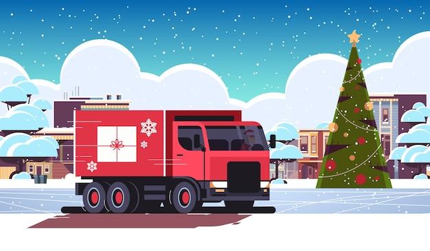 Papá noel que conduce la furgoneta de reparto con el transporte del envío del envase de la caja de regalo para el concepto de la celebración de las vacaciones de invierno de la feliz navidad ilustración del vector plano horizontal del paisaje urbano nevado