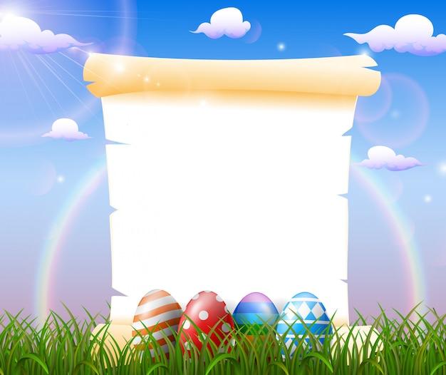 Papel en blanco en el campo de hierba con huevos de pascua decorados